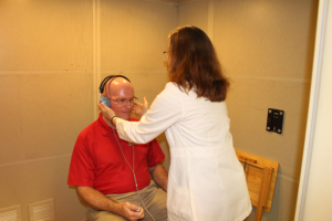 Dr. Laura Bradley Pratesi showing Eddie Hill audiology tests she uses for her clients